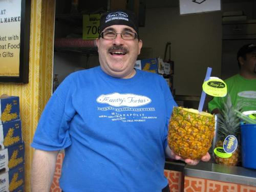 A smiling Manny Gonzalez holding a pineapple with the top cut off.
