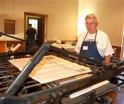Photo of a man at a large printing press