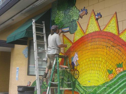 Picture of a man putting the finishing touches on a mosaic including a bright sun.